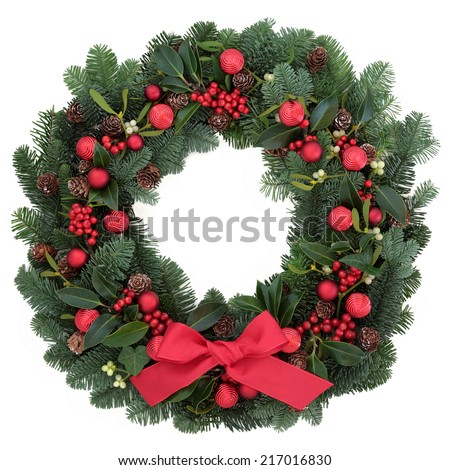 Christmas wreath with red bauble decorations and bow, holly, ivy, mistletoe, fir and pine cones over white background. - stock photo