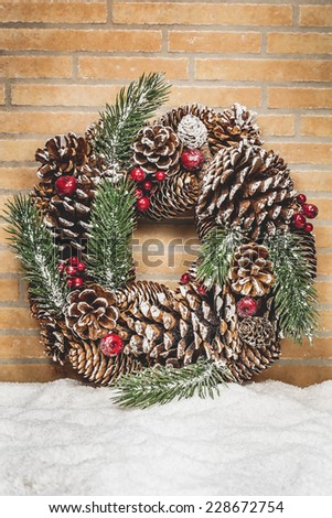 Christmas wreath with red berry and pine cone on a rustic wall with copy space with a snow. Holiday background.  Done with a vintage retro filter. Macro, selective focus - stock photo