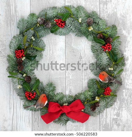 Christmas wreath with robin decorations, red bow, holly, mistletoe and snow covered blue spruce fir over distressed white wood front door background.