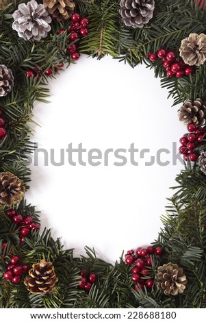 Christmas wreath with traditional decorations and berries in snow. Space for copy.