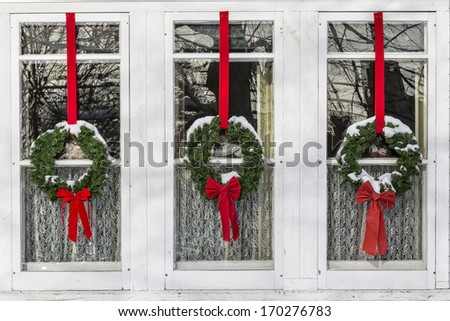 Christmas wreaths covered in snow hanging in front of lace curtained windows.