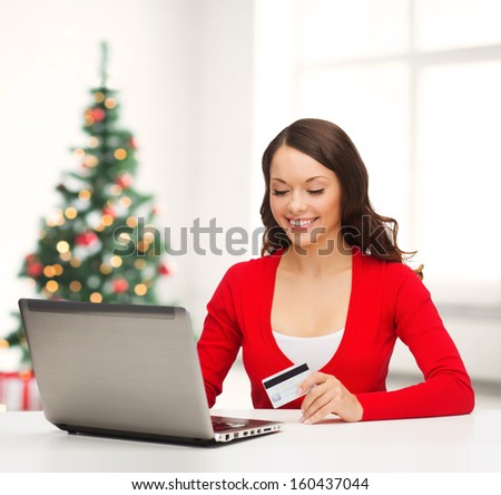 christmas, x-mas, electronics, gadget concept - smiling woman in red clothes with laptop computer and credit card - stock photo