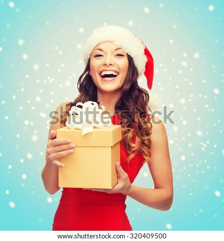christmas, x-mas, new year, winter, happiness concept - smiling woman in santa helper hat with gift box - stock photo