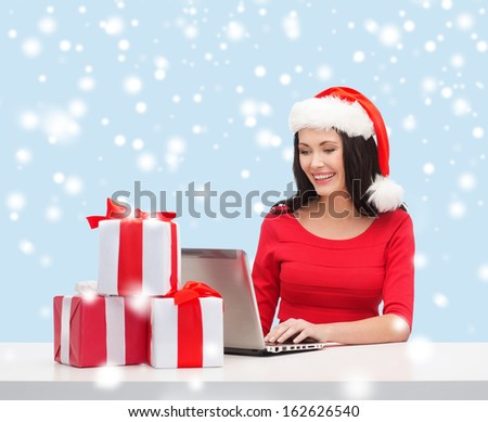 christmas, x-mas, online shopping concept - woman in santa helper hat with gift boxes and laptop computer