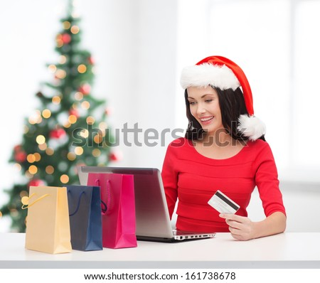 christmas, x-mas, online shopping concept - woman in santa helper hat with shoopping bags, laptop computer and credit card - stock photo