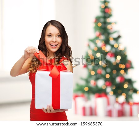 Celebration concept smiling woman in red dress with many gift boxes