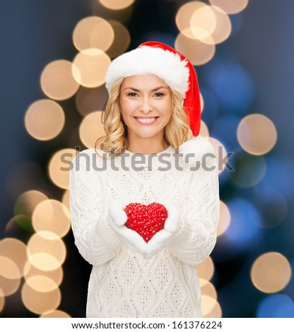 christmas, x-mas, winter, charity, love, happiness concept - smiling woman in santa helper hat with red heart - stock photo