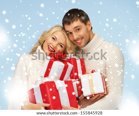christmas, x-mas, winter, happiness concept - happy man and woman with many gift boxes