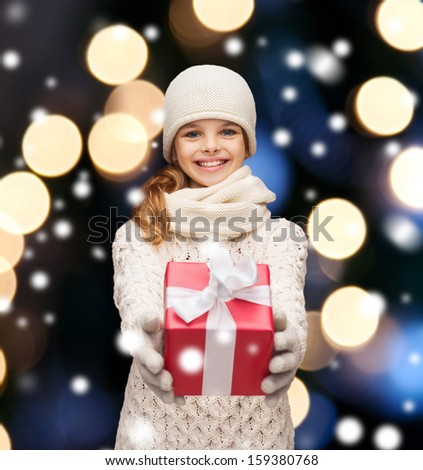 christmas, x-mas, winter, happiness concept - smiling girl in hat, muffler and gloves with gift box - stock photo