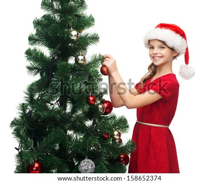 christmas, x-mas, winter, happiness concept - smiling girl in santa helper hat decorating a tree - stock photo