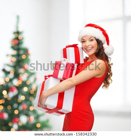 christmas, x-mas, winter, happiness concept - smiling woman in santa helper hat with many gift boxes - stock photo