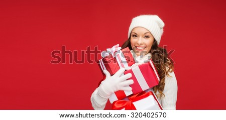 christmas, x-mas, winter, happiness concept - smiling woman in sweater and hat with many gift boxes - stock photo