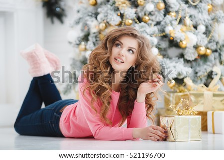 christmas, x-mas, winter, happiness concept - smiling woman with many gift boxes. Girl opens a gift against the background of the Christmas tree. happy young woman celebrating Christmas