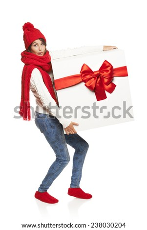 Christmas, x-mas, winter, happiness concept. Surprised excited woman in winter clothing carrying huge heavy gift box with red bow, in full length, isolated on white - stock photo