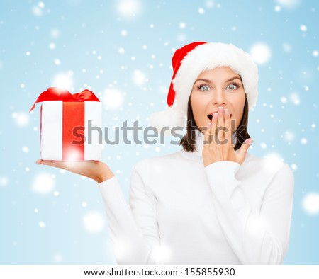 christmas, x-mas, winter, happiness concept - surprised woman in santa helper hat with gift box - stock photo