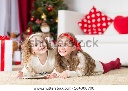 christmas, x-mas, winter, happiness concept - two adorable curly girls playing with tablet pc  - stock photo