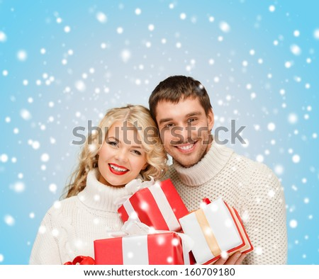 christmas, x-mas, winter, valentine's day, birthday, couple, happiness concept - smiling woman and man with many gift boxes
