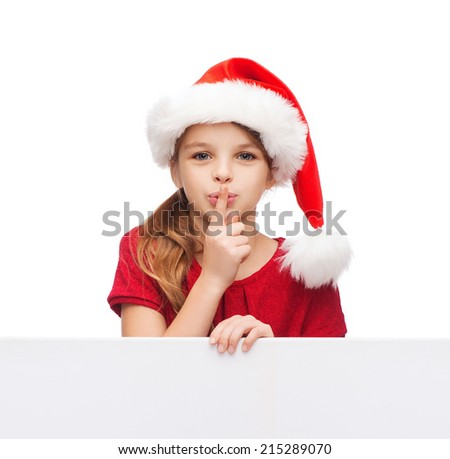 christmas, xmas, holidays and advertisement concept - happy girl child in santa helper hat with blank white board making shh gesture - stock photo