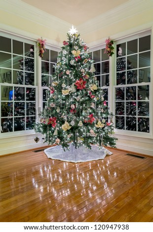 Christmas xmas tree decorated in a modern home with lights reflecting off wooden floor - stock photo