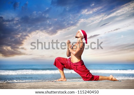 Christmas yoga surya namaskar by man in red trousers and Christmas hat on the beach near the ocean in India - stock photo