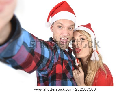 Christmas young beautiful couple in Santa hats in love taking romantic self portrait selfie photo together with mobile phone smiling happy wearing trendy clothes