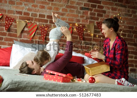 Christmas. Young family has a rest. The room is festively decorated. Boxes with Christmas gifts are not opened yet. The father cheerfully plays with the little daughter. Mother sits next and laughs.