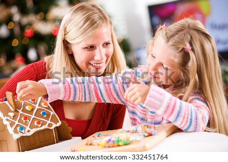 Christmas: Young Girl Uses Candy To Decorate Gingerbread House While Mother Watches - stock photo