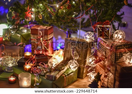 Christmastime, a lot of beautiful gifts under the Christmas  tree illuminated in the warm atmosphere of Christmas - stock photo