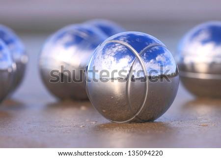 Chrome boules on a sandy beach. - stock photo