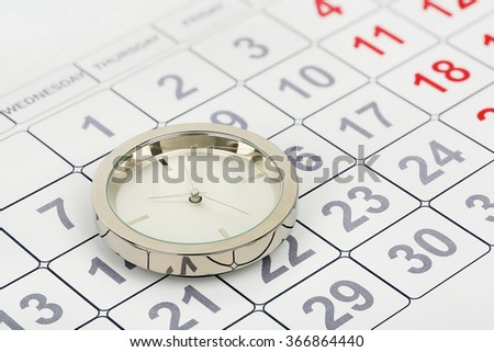 chrome clock on calendar, abstract time concept - stock photo