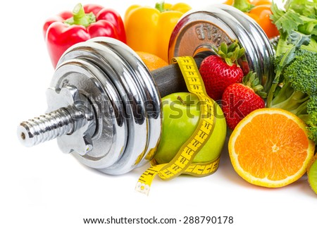 Chrome dumbbells surrounded with healthy fruits and vegetables on a white background. - stock photo