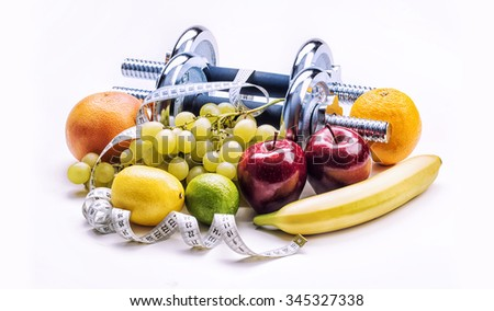 Chrome dumbbells surrounded with healthy fruits measuring tape on a  white background with shadows. Healthy lifestyle diet and exercise. - stock photo