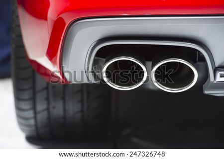 Chrome exhaust pipe of red powerful sport car bumper - stock photo