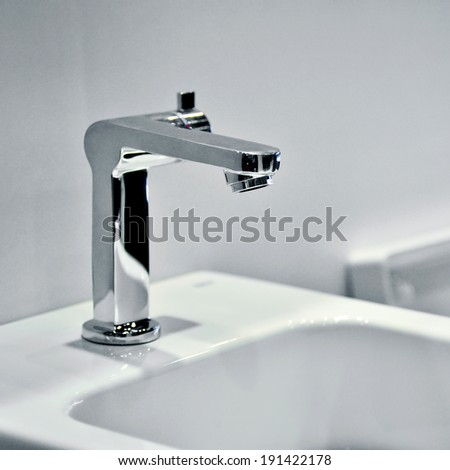 Chrome faucet with washbasin in modern bathroom - stock photo