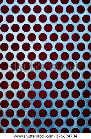 Chrome grid with round holes over a red background - stock photo