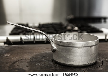 Chrome pot standing on hotplate in professional kitchen