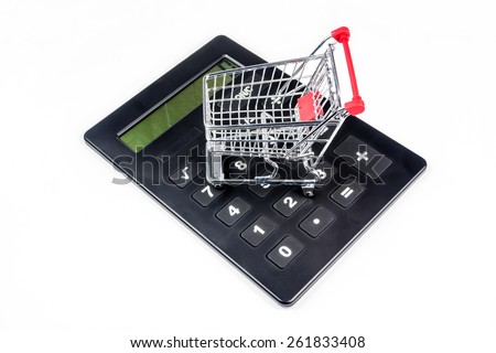 chrome shopping cart standing on black big calculator