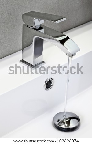 chrome tap in modern bathroom - stock photo