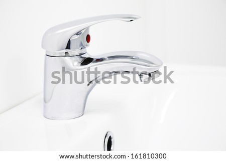chrome water tap on the white bathroom - stock photo