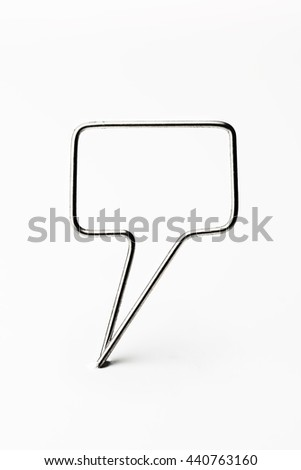 Chrome wire tweet or remark. Blank speech bubble made of chrome wire isolated on white. Ready for inserting text. Shallow depth of field. - stock photo