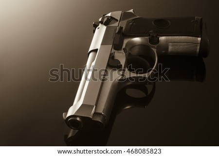 Chromed handgun on black background with reflection