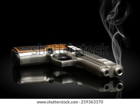 Chromed handgun on black background with smoke - stock photo