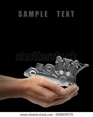 chromed motorcycle engine. Man hand holding object  isolated on black background. High resolution