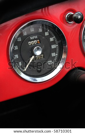 Chromed vintage speedometer in dash of classic red sports car