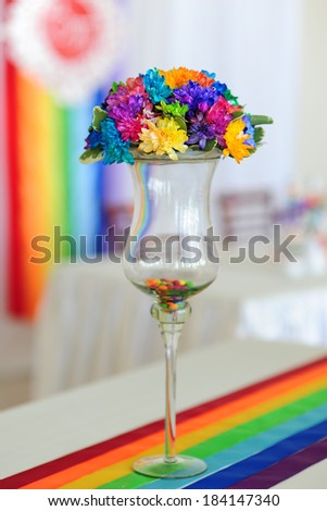 chrysanthemum bouquet in a glass vase on a wooden table stands in the interior with light-colored walls and dark chairs - stock photo