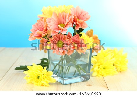 Chrysanthemum flowers in vase on wooden table on natural background - stock photo