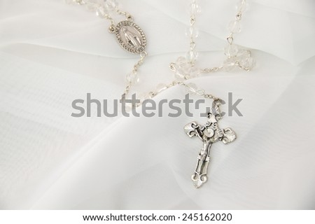 Chrystal Rosary beads with a Silver Crucifix on a cloud of white organza - stock photo