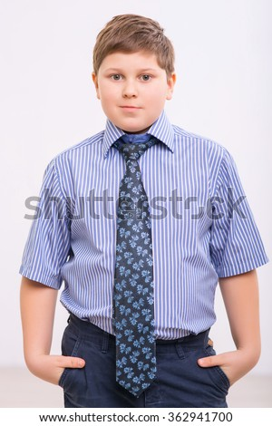 Chubby boy is standing with hands in pockets. - stock photo