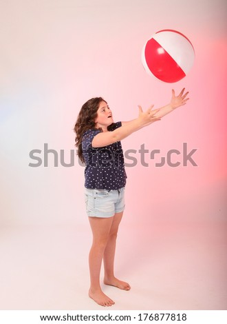 Chubby brunette girl playing ball - stock photo