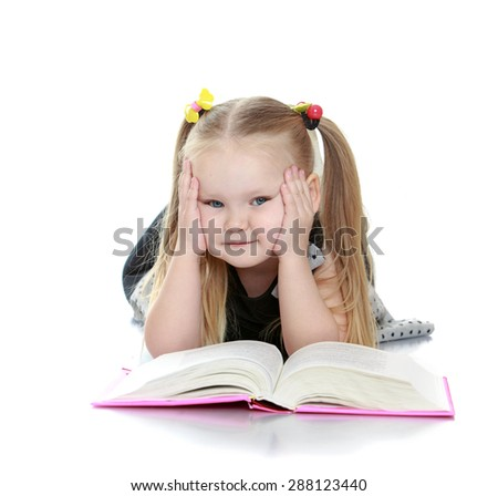 Chubby little blonde girl reading a book lying on the floor-isolated on white background